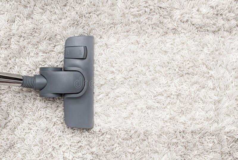 Staubsauger säubert den weißen rauhaarigen Teppich lizenzfreies stockbild