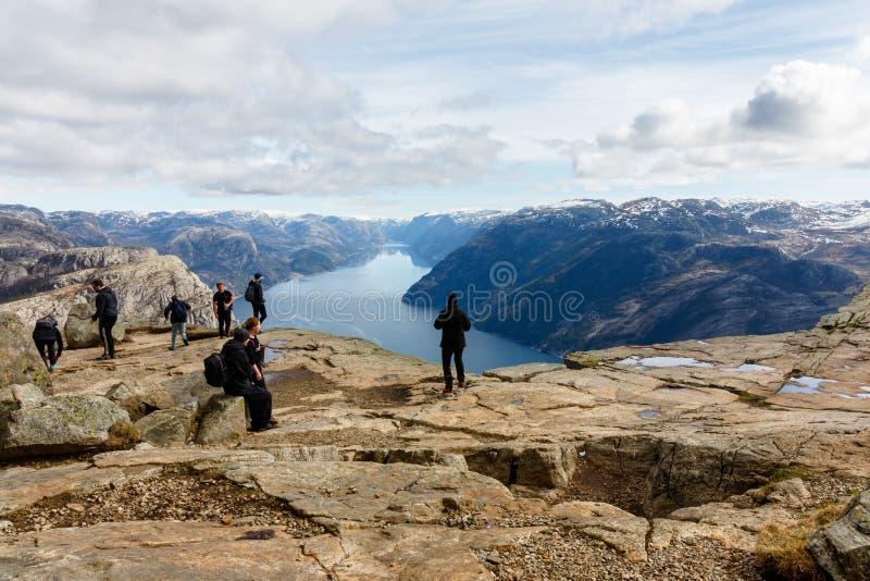 Stavanger, Norvegia - 16 aprile 2016: La gente che sta a Preikestolen, la roccia del quadro di comando Lysefjorden nei precedenti fotografie stock