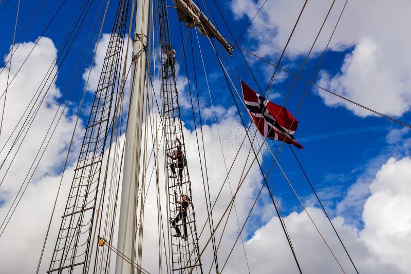 STAVANGER, NORWAY - CIRCA SEPTEMBER 2016: Three crew members climb up a Norwegian ship`s mast. STAVANGER, NORWAY - CIRCA SEPTEMBER 2016: Three crew members climb stock photos