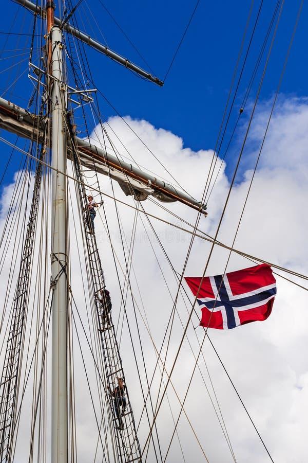 STAVANGER, NORWEGEN - CIRCA IM SEPTEMBER 2016: Drei Mannschaftsmitglieder klettern oben einen norwegischen Schiff ` s Mast stockfoto