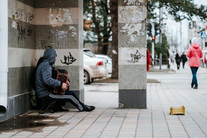 Stavropol Rosja, Marzec, - 03, 2019: Bezdomni g?odni muzyk?w ?ebracy z akordeonem pytaj? dla datk?w na ulicznej pobliskiej ?ciani zdjęcie stock