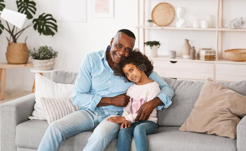 Stay at home. African American family of granddad and granddaughter embracing indoors. Panorama. Stay at home concept. African American family of granddad and stock image