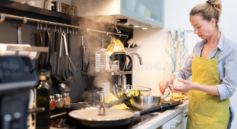 Stay at home housewife woman cooking in kitchen, salting dish in a saucepan, preparing food for family dinner. royalty free stock photo