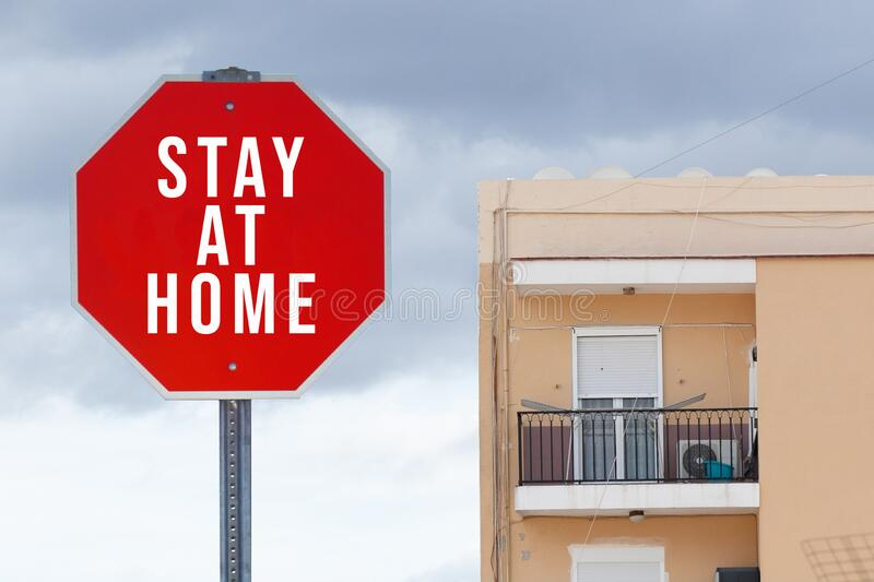 Stay at home red stop sign with apartment building in the background - coronavirus crisis campaign.  royalty free stock images