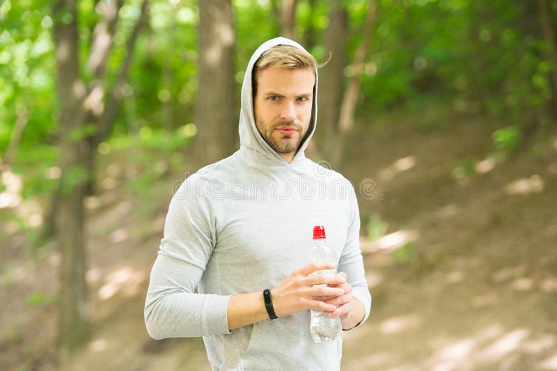 Stay hydrated. Athlete drink water after training in park. Vitamins and minerals. Man athletic sportsman hold bottle. Water. Man athlete sport clothes care royalty free stock photo