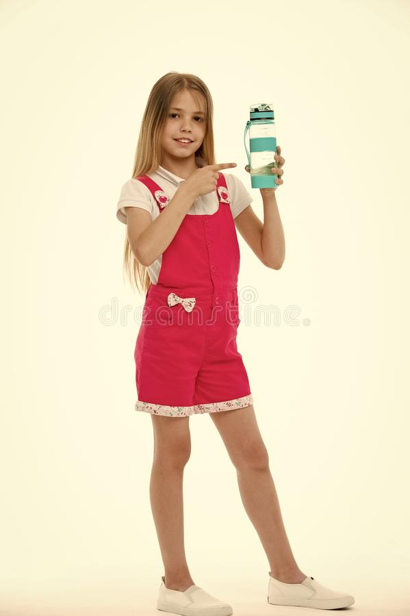 Stay hydrated. Girl cares about health and water balance. Girl on smiling face posing with water bottle isolated white. Background. Kid girl long hair pointing stock images