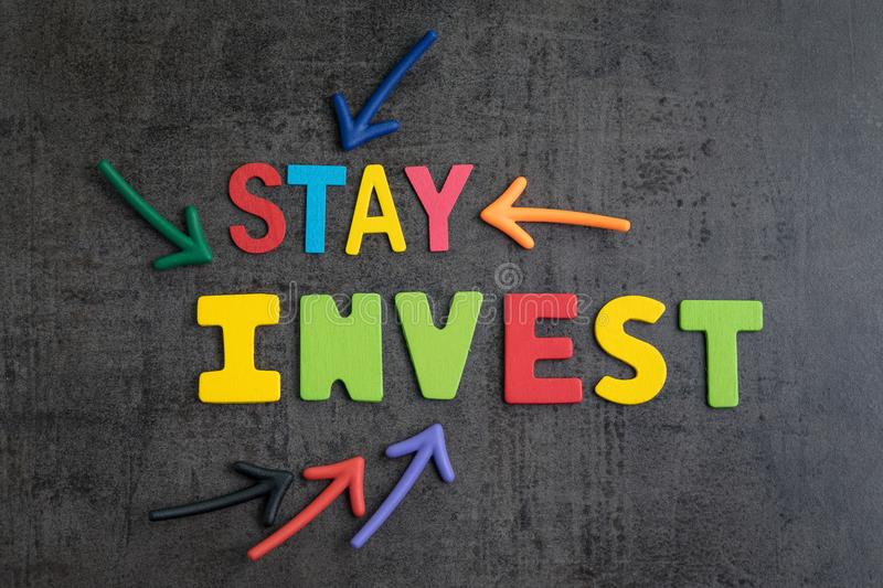 Stay invested in stock with no market timing concept, arrows pointing to words STAY INVEST on loft cement wall stock images