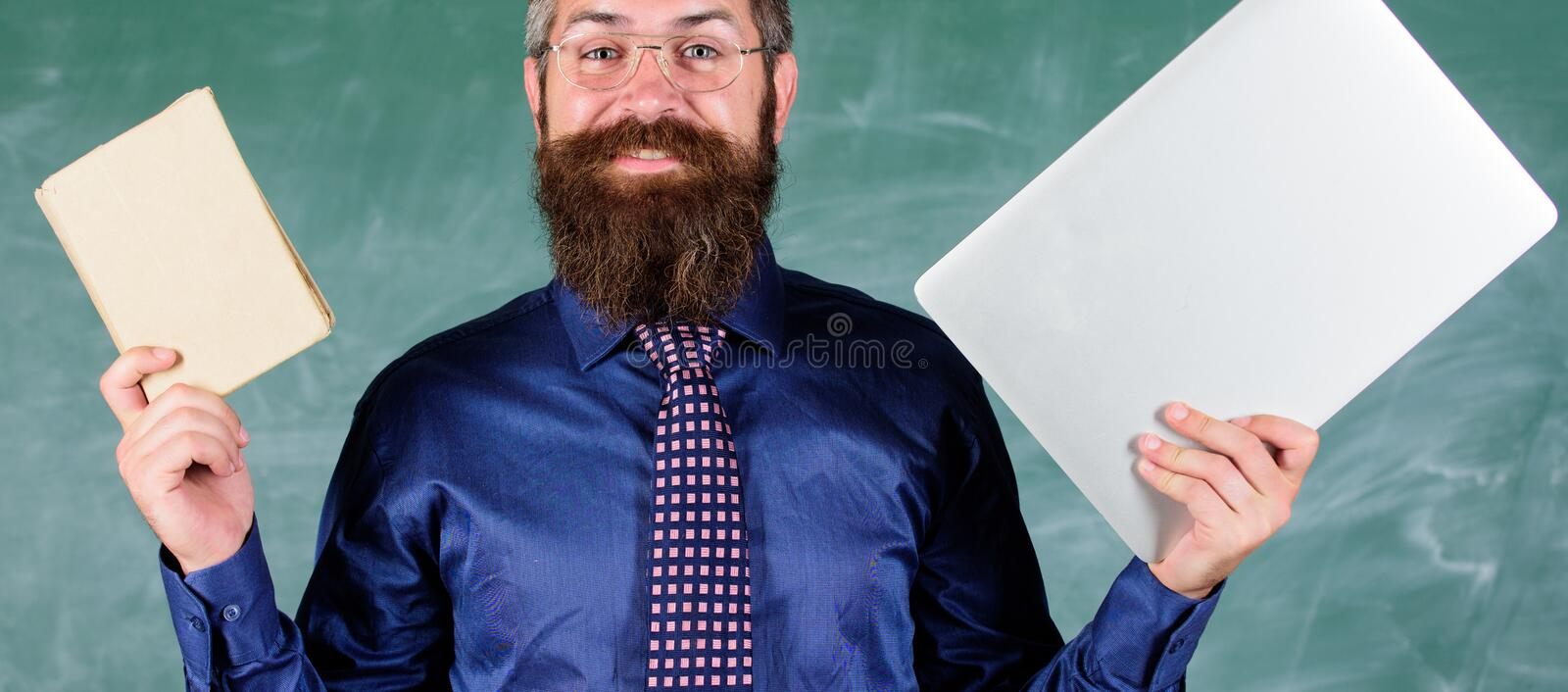 Stay modern with technology. Teacher bearded hipster holds book and laptop. Choose right teaching method. Teacher royalty free stock photography