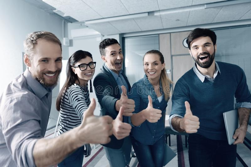 Positive young group of people thumbing up in the office stock photography