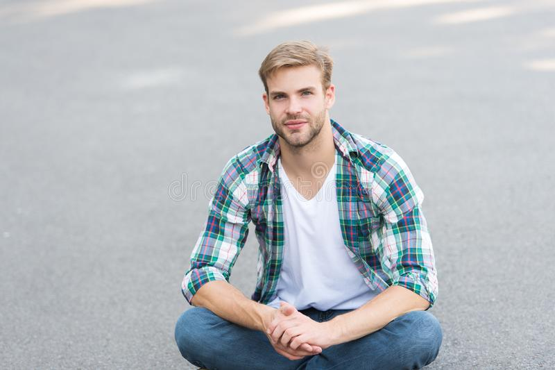 Stay relaxed. handsome man checkered shirt. male fashion. student relax on road. macho guy outdoor. street style. man royalty free stock photography
