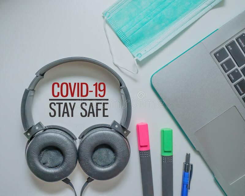 COVID-19 STAY SAFE. Stay safe advice to stop coronavirus COVID-19 spreading. Global pandemic Covid-19 prevention. Headphone, medical mask, pencil and laptop stock images