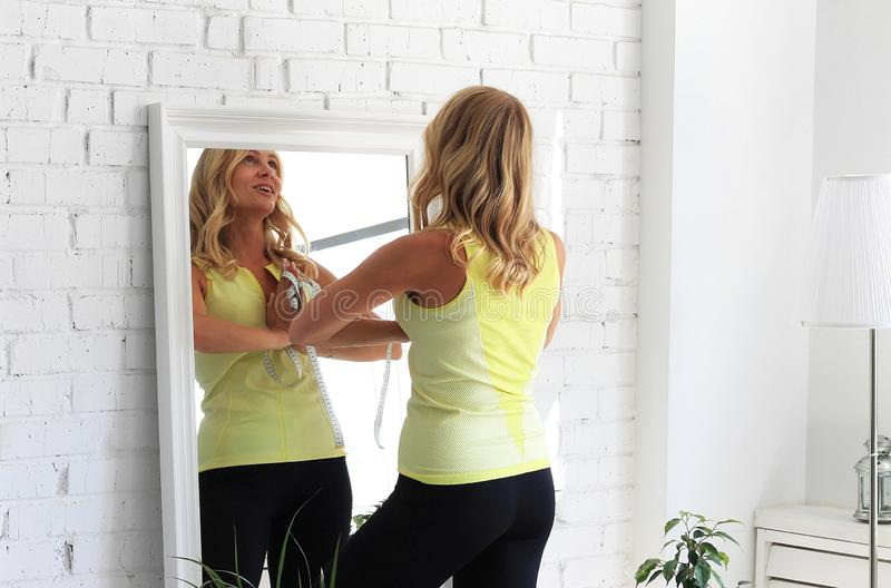 Stay in shape. Attractive woman with athletic body going to measure the waist with a measure type in front of a mirror royalty free stock photos