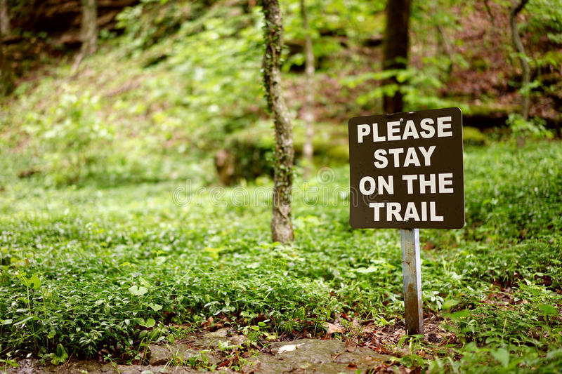Stay on the trail sign. Park sign directs visitors to correct walking path. Out-of-the-box thinking is not allowed royalty free stock photography