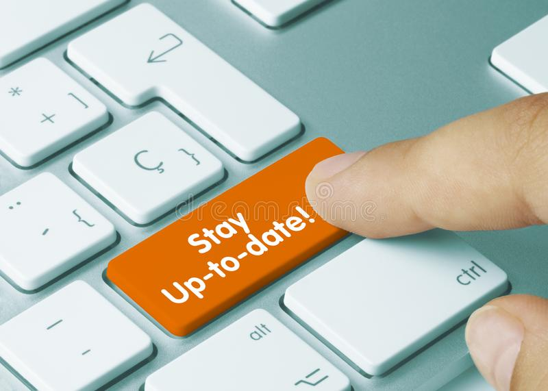 Stay Up-to-date! - Inscription on Orange Keyboard Key. Stay Up-to-date! Written on Orange Key of Metallic Keyboard. Finger pressing key stock photo