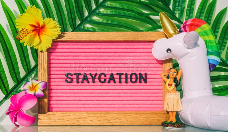 Staycation sign for summer vacation plans during COVID-19. Funny vintage hawaiian pink felt board text for staying home royalty free stock photos