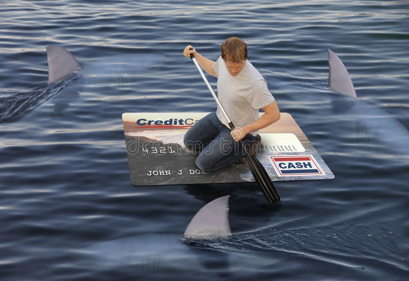 Staying Afloat. Man stranded on a raft made of a huge credit card in the ocean while being circled by sharks stock photo