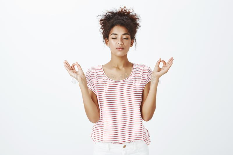 Staying calm and relaxed in urban atmosphere. Cute determined dark-skinned woman in striped t-shirt, closing eyes and. Raising hands in zen gesture, meditating royalty free stock photo