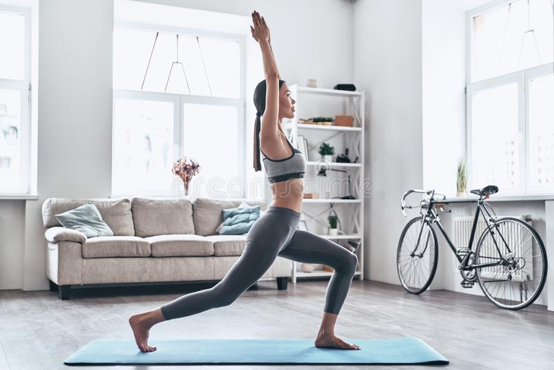 Staying fit and healthy. Beautiful young Asian woman in sports clothing doing yoga while relaxing at home stock image