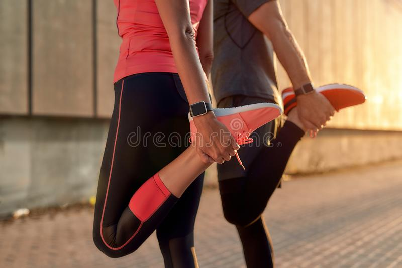 Staying flexible. Cropped photo of fitness couple in sports clothing doing stretching exercises together outdoors royalty free stock photos