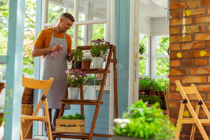 Cheerful florist sprinkling all of the plants outside. Staying fresh. Cheerful florist with a sprinkling can sprinkling all of the flowers outside his shop royalty free stock photo