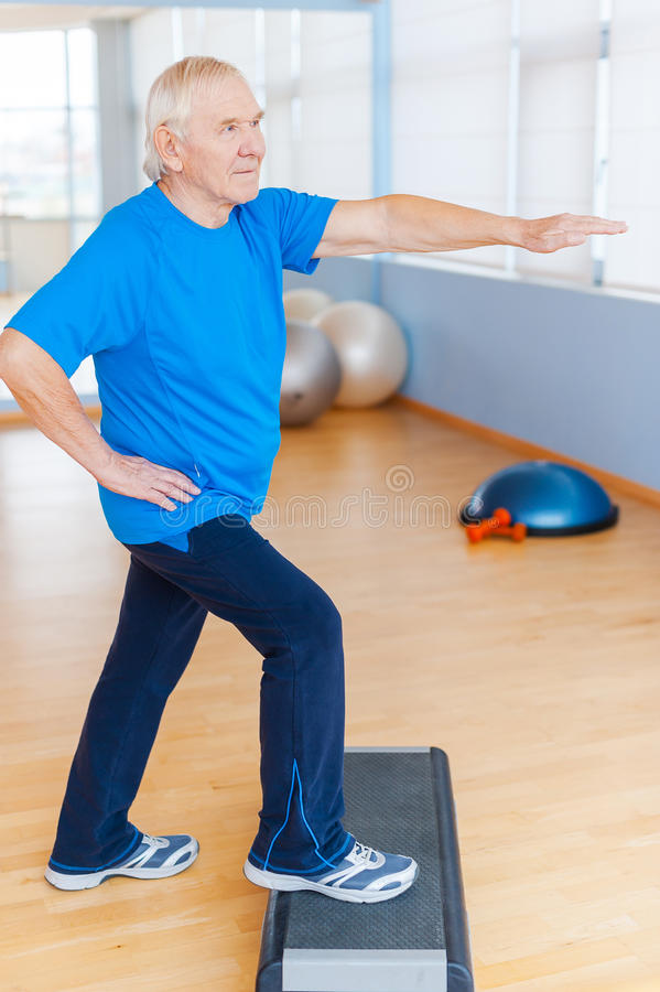 Staying healthy and active. Full Length of confident senior man doing step aerobics in health club stock photography