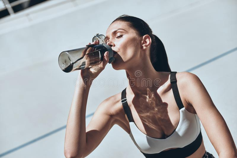 Staying hydrated. Beautiful young woman in sports clothing drinking water while sitting on the running track outdoors stock image