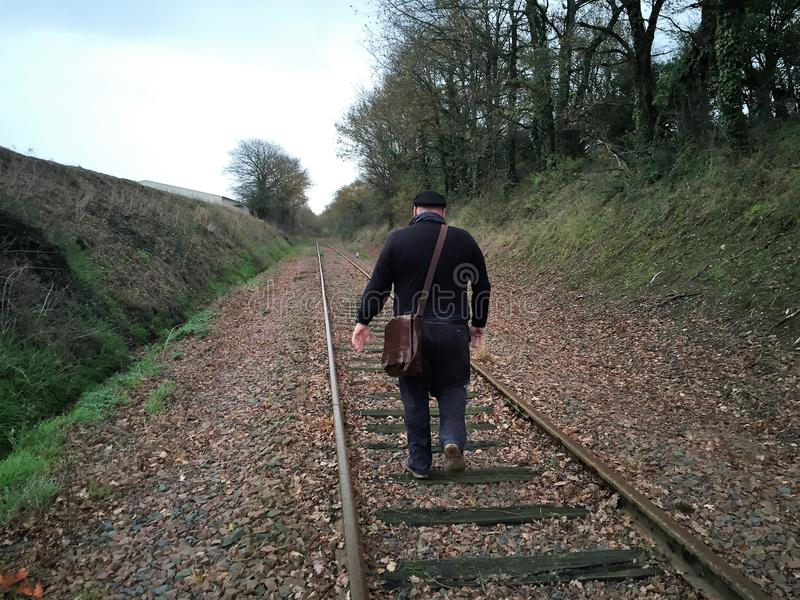 A man walks along the railroad tracks. royalty free stock photography