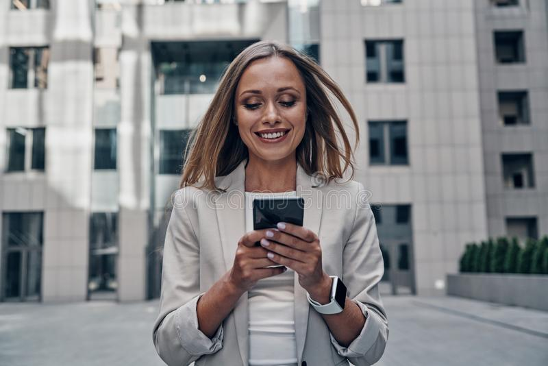 Staying in touch. Beautiful young woman in suit using smart phone and smiling while standing outdoors royalty free stock photography