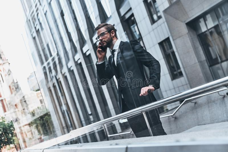 Staying in touch. Good looking young man in full suit talking on the phone while standing outdoors royalty free stock images