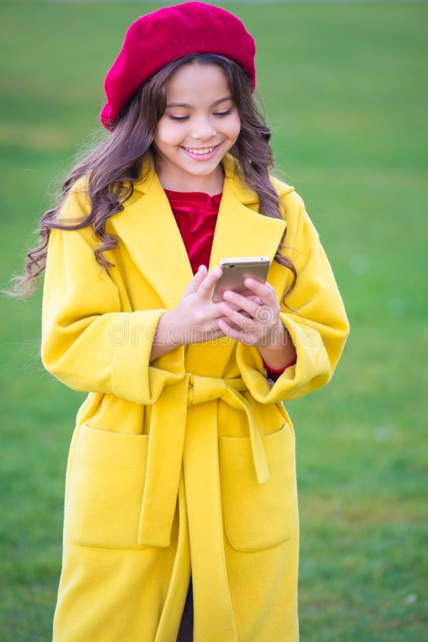 Staying in touch. Happy girl read sms in mobile phone. Little girl use mobile internet on autumn day. Happy childhood. And modern life. Enjoying autumn time royalty free stock photo