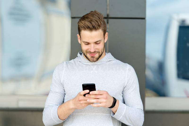 Staying in touch. Man with beard walks with smartphone, urban background. Guy use smartphone to send message stay in royalty free stock photography