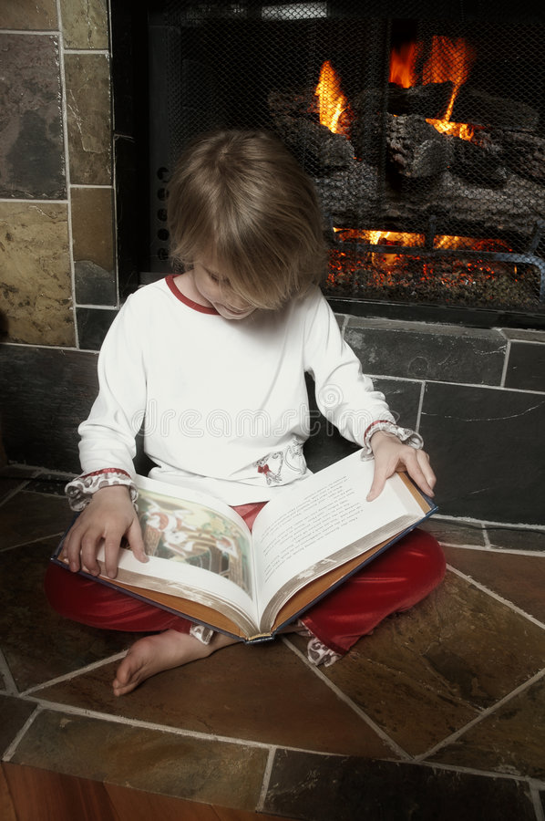 Staying Warm. Little girl reads her book by the warmth of the fireplace in winter. Image has soft filter effect with some de-saturation to give dreamy effect royalty free stock image