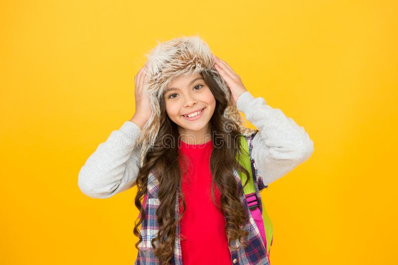Staying warm in winter. Happy little girl in winter fashion. Small child smiling in fur hat on yellow background. Cute stock photos
