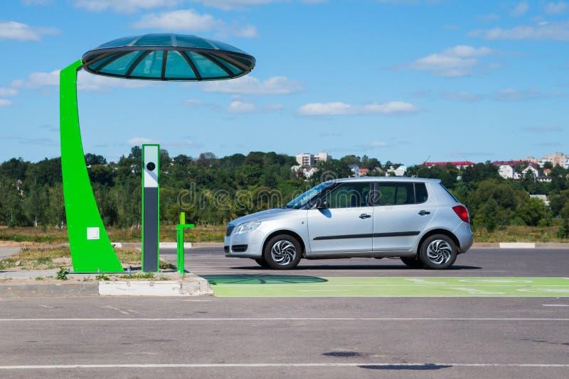 Stazione di carico elettrica con l'automobile eclettica fotografie stock libere da diritti