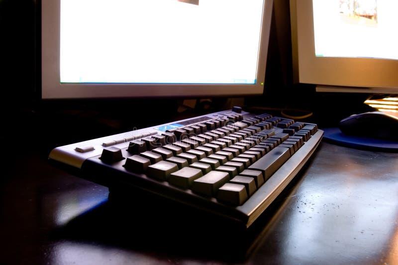 Stazione di lavoro del calcolatore con due videi sullo scrittorio della parte superiore del metallo fotografie stock libere da diritti