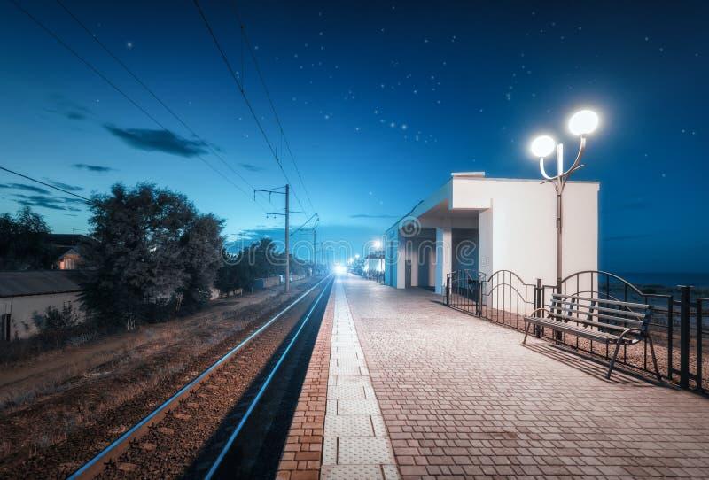 Stazione ferroviaria alla notte di estate Cielo stellato sopra la ferrovia al crepuscolo fotografia stock