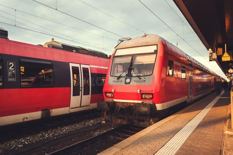 Stazione ferroviaria bella con il treno pendolare rosso moderno al tramonto immagini stock