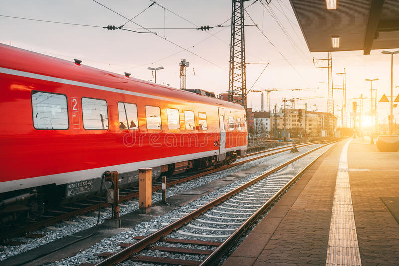 Stazione ferroviaria bella con il treno pendolare rosso moderno al tramonto fotografia stock