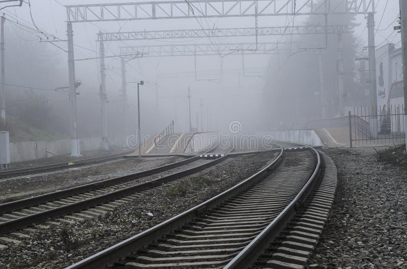 Stazione ferroviaria con una nebbia d'avvicinamento fotografia stock libera da diritti