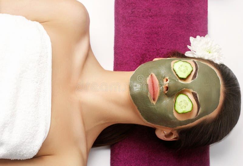 Stazione termale Clay Mask Donna con la maschera facciale dell'argilla e cetrioli sull'occhio fotografie stock libere da diritti