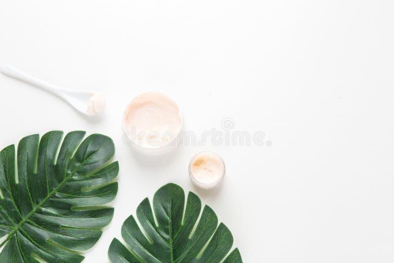 Stazione termale del corpo e facciale crema di fronte sui precedenti delle foglie tropicali della palma di Monstera fotografie stock libere da diritti