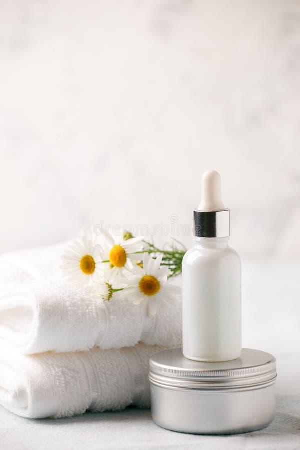 Stazione termale e regolazione di benessere Composizione con i fiori della camomilla e la bottiglia cosmetica del siero e della c immagini stock libere da diritti