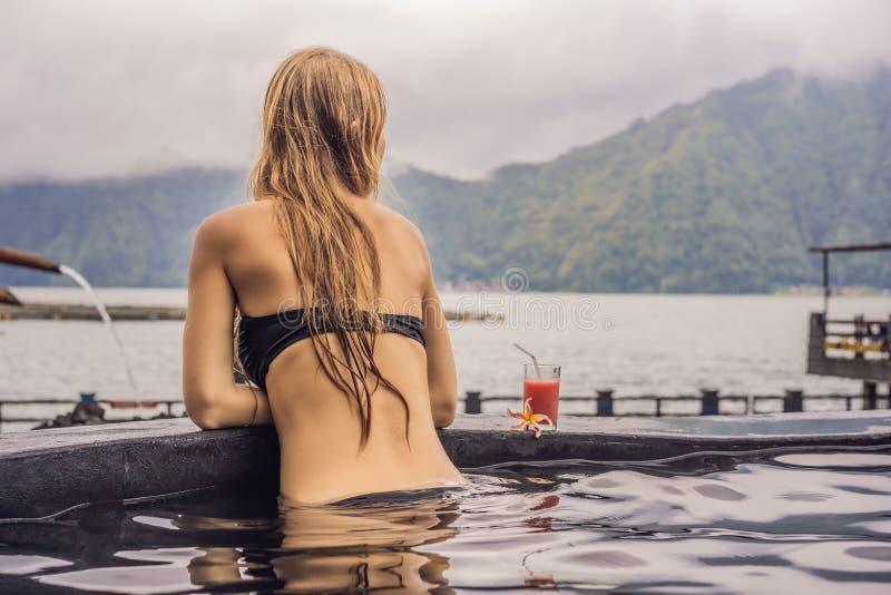 Stazione termale geotermica Donna che si rilassa nello stagno della sorgente di acqua calda contro il lago concetto delle sorgent fotografia stock