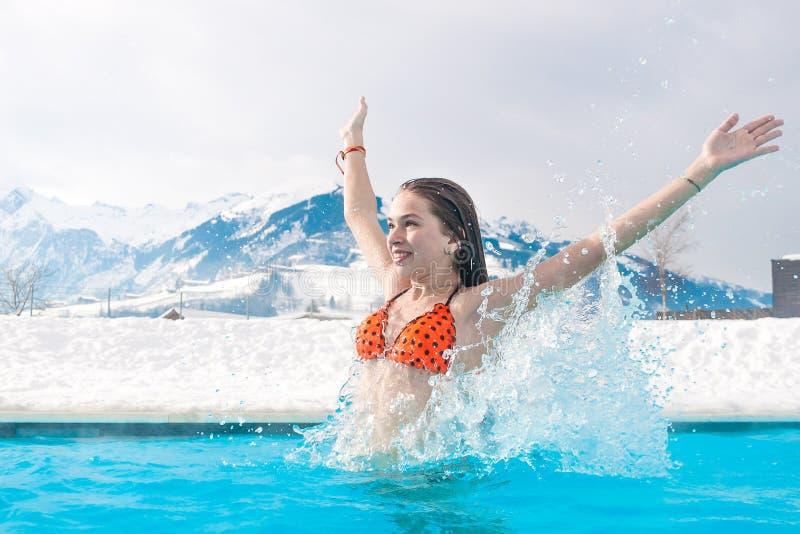 Stazione termale geotermica La ragazza gode di di nuotare in acqua blu sui precedenti delle montagne nevose immagini stock libere da diritti