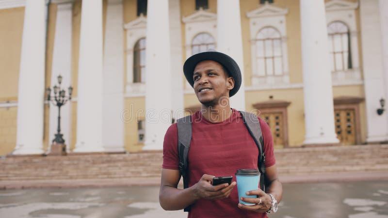 Steadicam schoss von lächelndem touristischem Mann gehendem und surfendem Smartphone nahe berühmtem historischem Platz in Europa stockbild