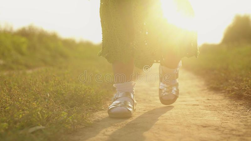 Steadicam shot of baby girl walking along rural field pathway on a sunny day, feet close-up royalty free stock images