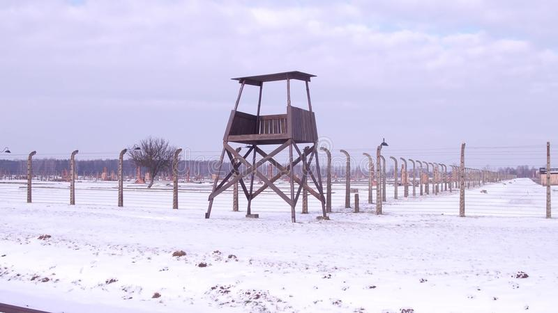 Steadicam shot of old guard tower and barbed wire fence. Concentration camp in winter stock images