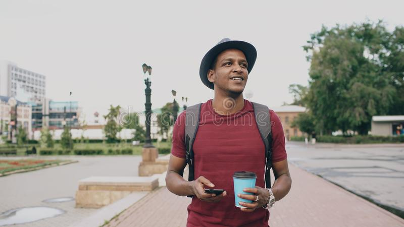 Steadicam shot of smiling student in hat walking and surfing smartphone drinking coffee outdoors stock photography