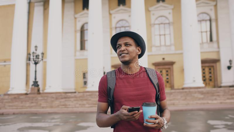 Steadicam shot of smiling tourist man walking and surfing smartphone near famous historical place in Europe stock image