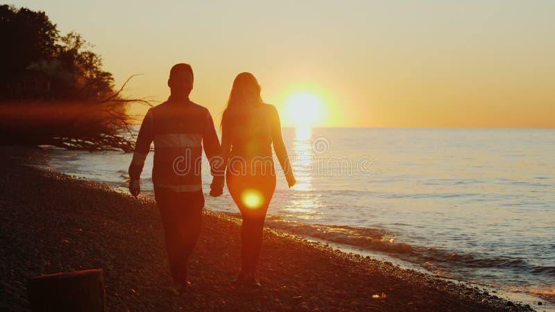 Steadicam tiró: pares multi-étnicos jovenes que llevan a cabo las manos, caminando a lo largo de la costa en la puesta del sol Ho foto de archivo